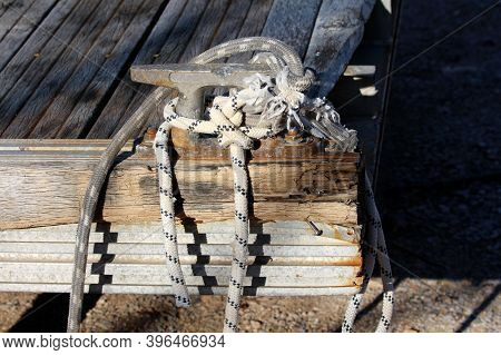 Heavily Used Two Old Ropes With Different Designs And Color Wrapped Around Strong Iron Mooring Bolla