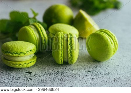 Macaroons. Green Macaroons With Lime And Mint Leaves. Delicious French Desserts. Macaroons On The Ta