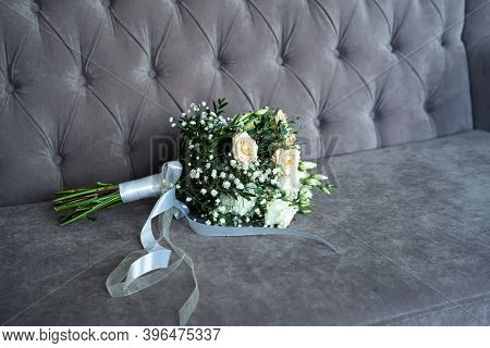 Wedding Bouquet Of White  Flowers And Green Leaves On The Sofa.