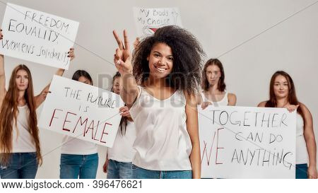 Young African American Woman In White Shirt Showing Peace Sign, Smiling At Camera. Group Of Diverse