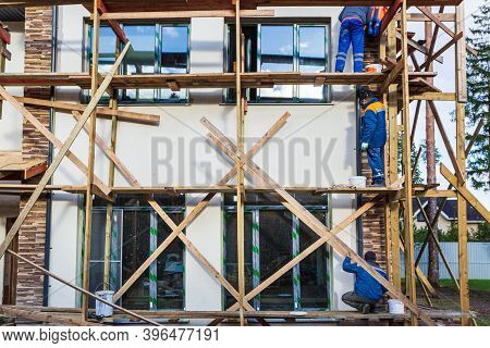 Workers Are Painting The Facade From Wooden Platform In House Is Under Construction, Remodeling, Ren