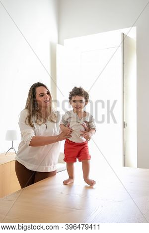 Joyful Kid Trying To Walk With Moms Support. Happy Mom Helping Baby To Take First Steps On Table. Fr