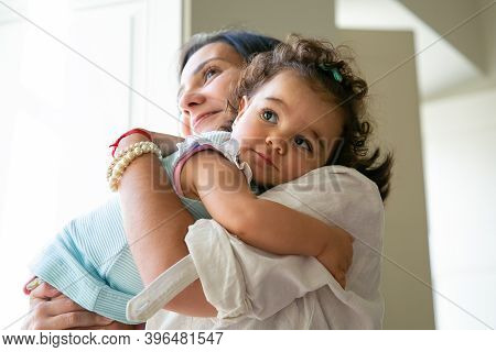 Happy Mom Hugging And Holding Sweet Baby Daughter In Arms. Cute Curly Haired Little Girl Looking At