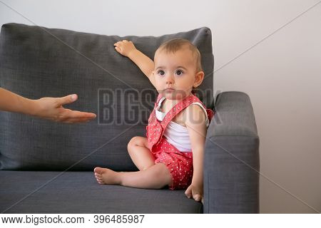 Funny Little Baby Sitting On Grey Sofa And Looking At Unrecognizable Person. Someone Giving Hand To