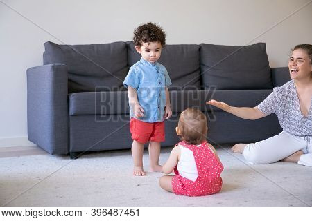Serious Mix-raced Boy Standing And Looking At Baby. Caucasian Pretty Mom Talking Something To Childr