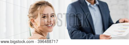 Female Executive Looking At Camera With Blurred Co-worker On Background, Banner