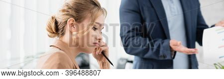 Businesswoman With Pen Looking Down With Blurred Co-worker On Background, Banner