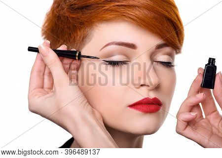 Makeup Artist Applying Black Eyeliner Close-up. Beautiful Young Woman With Short Red Hair. Makeup De