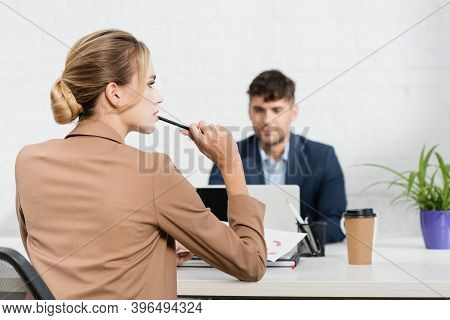 Back Of Thoughtful Businesswoman With Pen, Sitting At Workplace With Co-worker On Background