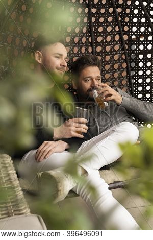Young Boyfriends Relaxing And Drinking Beer On The Balcony. Love And Affection Of Same Sex Partners.
