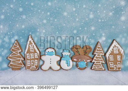 Christmas Ginger Cookies In Protective Masks Among Gingerbread Houses And Fir Trees. Concept Of Wint