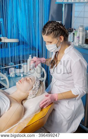 Darsonvalization Of The Face Or Rejuvenation Of The Face With The Help Of Electrotherapy. Photo Of D