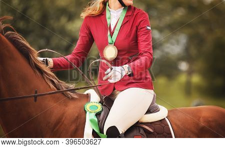 In The Saddle On A Sorrel Racehorse Sits A Woman In A Pink Suit With A Medal Around Neck, And A Priz
