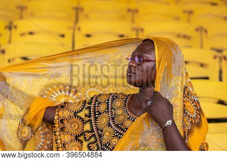 African Woman Holding In Her Head Shawl On An Empty Audience Stand In Accra Ghana West Africa