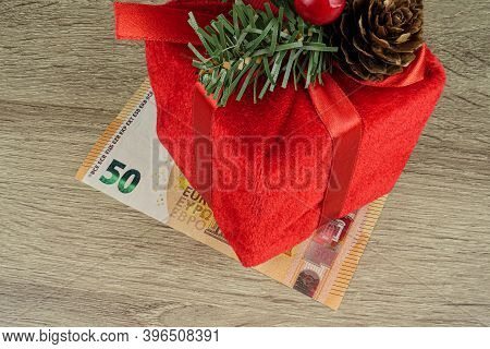 A Red Square Gift, The Packaging On Which A Red Bow, Wooden Background, Under Which Lies A Euro Bill