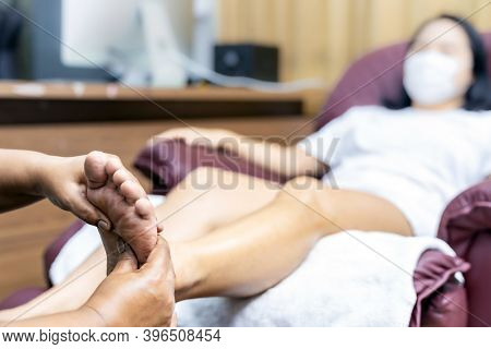 Close up asian woman do foot massage at home with face mask while city lockdown for social distance due to coronavirus pandemic. Massage is one of service business that shutdown while city lockdown.