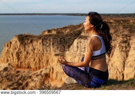 Mature Female Practicing Yoga Pose On Hill