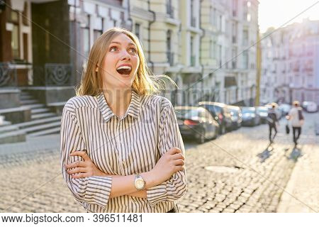 Beautiful Emotional Young Woman On A City Street. Female With Open Mouth, Emotion Surprise, Laughter