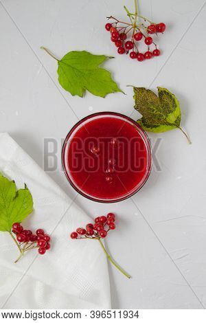 Viburnum Jam In Glass Bowl On The Light Grey Background Decorated With Viburnum Branches, Leaves, An