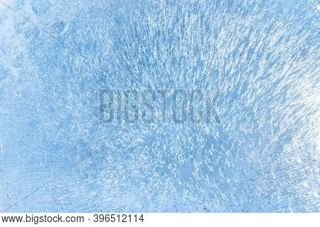 Blue Cracked Ice Background. Frozen Water, Sea. Frosty Winter Texture Of Thin Ice With Glare From Th