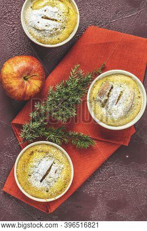Three Apple Pies In Ceramic Baking Molds Ramekin With Napkin, Apple, Spruce Branch, Cinnamon On Dark