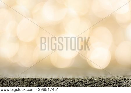 Golden bokeh background with wooden table close up