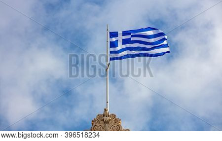 Greek Flag Waving On Pole Against Blue Cloudy Sky Background, Copy Space. Greece National Sign Symbo