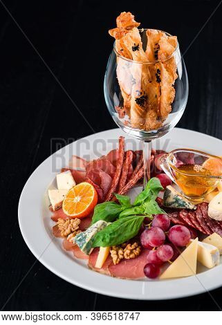 Antipasto Delicatessen - Sliced Meat, Ham, Salami, Cheese, Olives On Dark Table, Anti-paste On Black
