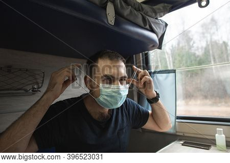 Young Caucasian Man Put On Medical Mask Travelling In A Train, Sitting Next To A Window. Man Protect
