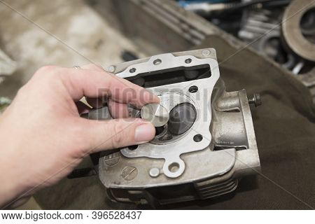 The Mechanical Picking The Intake-exhaust Valve For Overhaul  Motorcycle Engine. The Assembly Proces