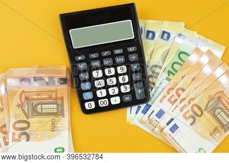 Above View Of Stacks Of Euro Bills And Calculator On Orange Background, Saving Or Spending Money Con