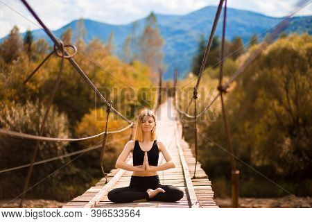 Woman Meditating In Lotus Position On Bridge Over Mountain River In Forest