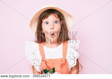 Little caucasian kid girl with long hair holding flower wearing spring hat scared and amazed with open mouth for surprise, disbelief face