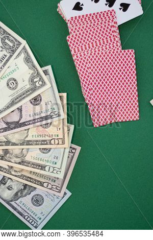 Dollars Banknotes Next To Playing Cards On A Green Background. Concept Of Losing Money, Playing For