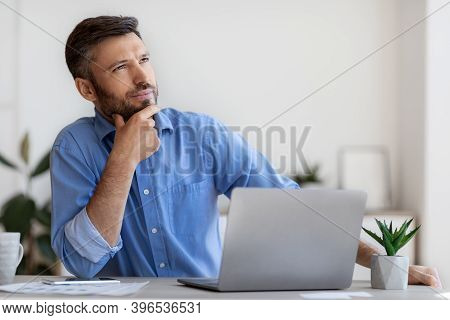 Portrait Of Pensive Millennial Businessman Thinking About Busines Project At Workplace, Handsome You