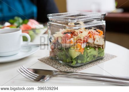 Glass Bowl Of Fresh Caesar Salad On A Table