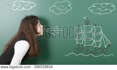 Pre-adolescent Girl Blowing On Painted Sailing Ship. Portrait Photo On School Board Background. High