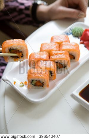 Woman Eating Japanese Sushi Rolls In Cafe