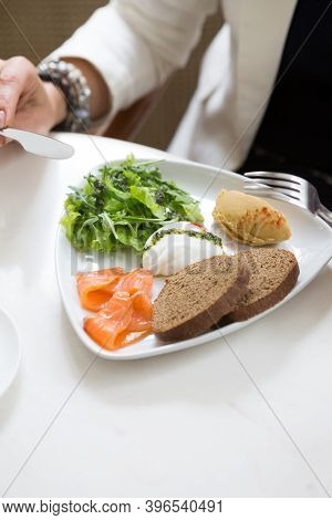 Woman Having Poached Egg For Breakfast At Cafe