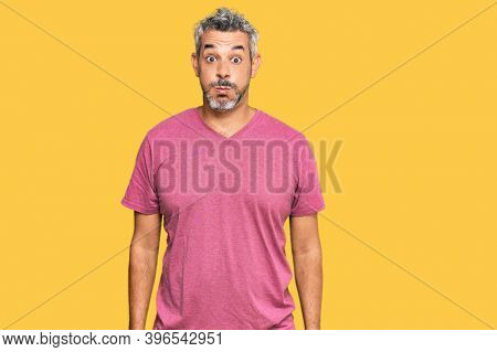 Middle age grey-haired man wearing casual clothes puffing cheeks with funny face. mouth inflated with air, crazy expression.