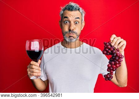 Middle age grey-haired man holding branch of fresh grapes and red wine puffing cheeks with funny face. mouth inflated with air, catching air.