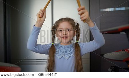 A Little Girl Plays Electronic Drums At Home. Cheerful Girl With Drum Sticks. Little Girl Playing On