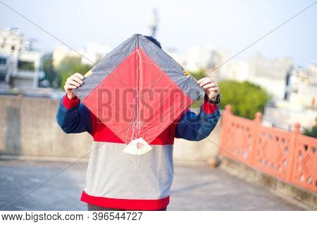 Lady Holding A Indian Fighting Kite Aloft In Order To Launch It On The Indian Harvest Festival Of Ma