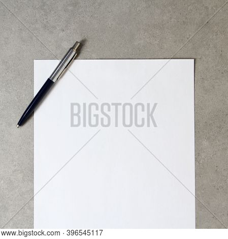 Template Of White Paper With A Ballpoint Pen On Light Grey Concrete Background. Concept Of New Idea,