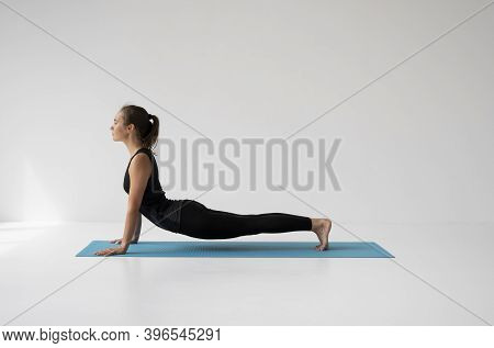 Young Woman Practicing Yoga, Lying And Stretching In Cobra Pose, Doing Bhujangasana Exercise. Attrac