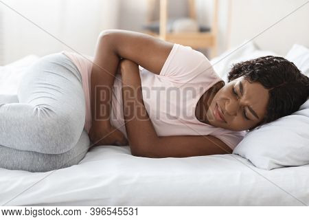 Period Pane. Frustrated Young Black Woman Touching Her Belly, Laying In Bed, Closeup, Copy Space. Sa