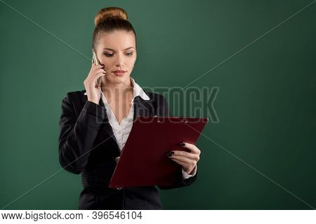 Pretty Businesswoman With Clipboard Talks On Phone Green Background