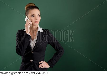 Smiling Pretty Businesswoman Talks On The Phone On Green Background