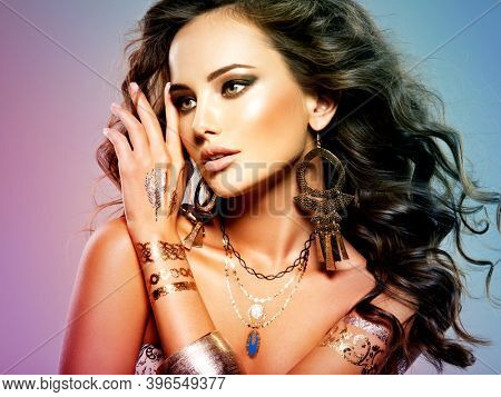 Woman Fashion Hair Jewelry Beautiful. Portrait of young adult sexy girl with brown hair. Golden jewelry. Brown makeup.