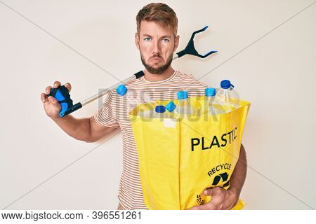 Young caucasian man holding recycling bag with plastic bottles and waste picker depressed and worry for distress, crying angry and afraid. sad expression.
